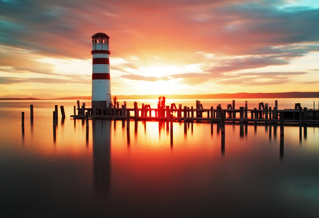 Beach sunset with lighthouse photo