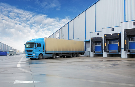 倉庫の建物で荷を下す貨物トラック 写真素材