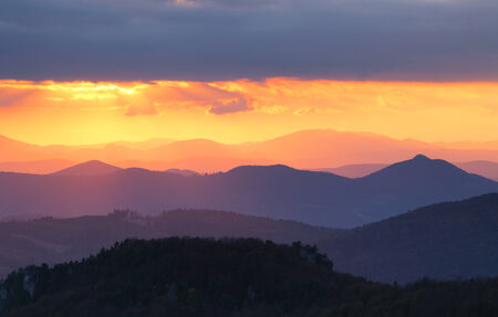 over the hill: Sunset over color mountain silhouette.