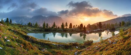 sunrise mountain: Mountain alps lake sunset panorama in Dolomites Stock Photo