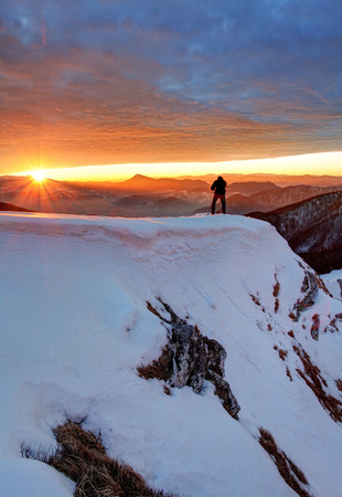 mountain landscape: Man on Top with sun in background Stock Photo