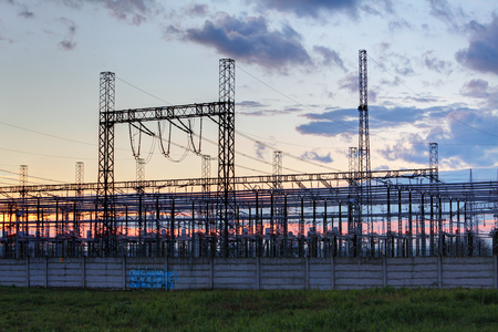 isolator high voltage: network at transformer station in sunrise, high voltage Stock Photo