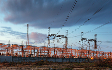 voltage: electricity transmission pylon silhouetted against blue sky at dusk