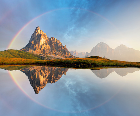 Rainbow over Mountain lake reflection, Dolomites, Passo Giau