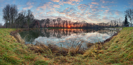 czech: Water reflection at sunrise in lake, panorama