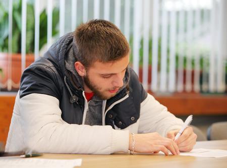 hombre escribiendo: Hombre joven atractivo que escribe una carta a mano