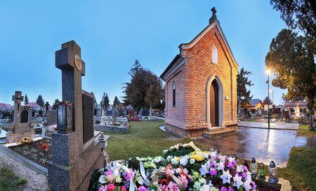 christian halloween: Cemetery panorama at night with chapel and flowers