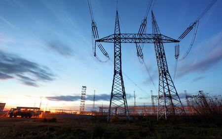 torres de alta tension: torre de transmisión eléctrica siluetas contra el cielo azul al atardecer Foto de archivo