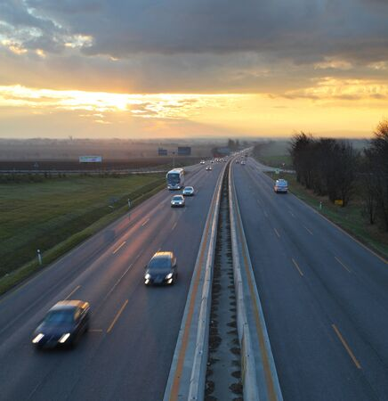 multiple lane highway: Car traffic against the sunset background.