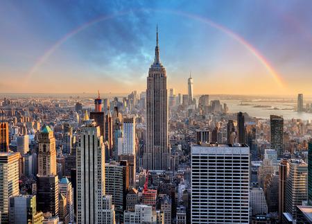 Skyline di New York City con grattacieli urbani e arcobaleno.