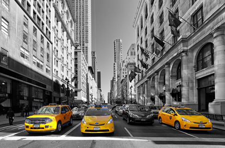 NEW YORK - APRIL 15: Yellow taxis rides on 5th Avenue on April 15 2016 in New York, USA. 5th Avenue is a central road of Manhattan, the most expensive shops and apartmens situated here