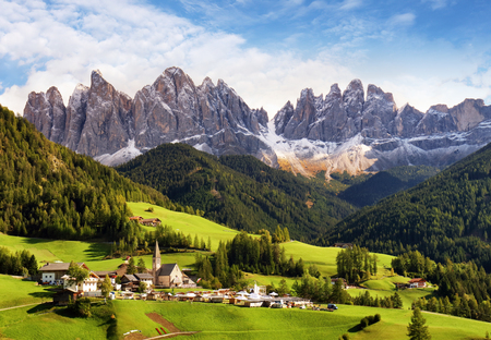 Val di Funes, Trentino Alto Adige, Italy. The great autumnal colors shines under the late sun with Odle on the background and Santa Magdalena Village on the foreground.