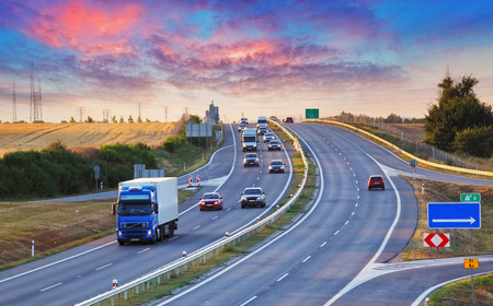 highway traffic: Highway traffic in sunset with cars and trucks Stock Photo