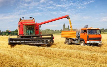 Harvester machine and tractor at harvest Stock Photo
