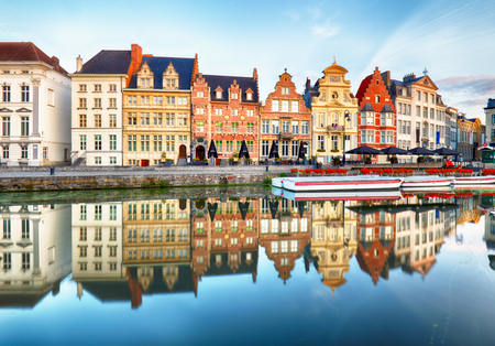 Gent, Belgium. Sunrise in historical center of Ghent with medieval buildings of Korenlei, Graslei and castle of the counts (Gravensteen) reflecting in water of river Leie Flanders, Belgium.
