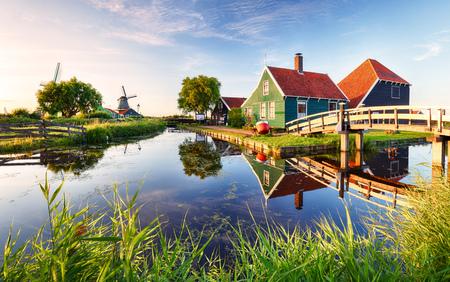 伝統的なオランダ風車、運河の近く。オランダ、夕暮れ時の景観