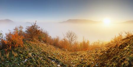 Sun over clouds mist in mountain landcape at sunrise