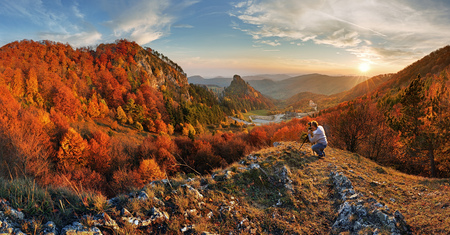 Photographer on top in mountain landscape