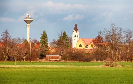 Church with green field in village Cifer, Slovakia