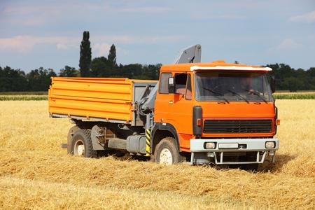 Car Truck on wheat field, harvesting Reklamní fotografie