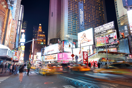 NEW YORK, USA - APRIL 12: The architecture of the famous Times Square in New York city, USA with its neon lights and panels at night and a lot of tourists passing by on April 12, 2016.