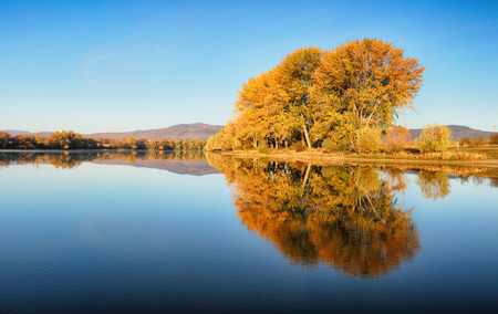 Autumn colorful trees under morning sunlight reflecting in tranquil river Reklamní fotografie