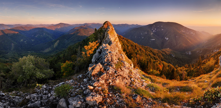 Mountain autumn panorama at sunset with forest and rocks.
