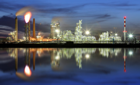 Oil refinery at night with reflection in water 写真素材