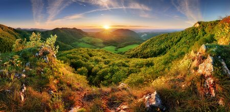Spring mountain landscape panorama with forest and sun 写真素材
