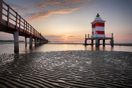 Wooden pier leading to a red lighthouse at sunrise in Lignano Sabbiadoro, Friuli, Italy - beach