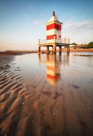 Red lighthouse at sunrise in Lignano Sabbiadoro on beach, Friuli, Italy