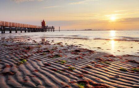 Sunrise with sun on beach with lighthouse in Italy - Lignano