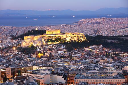 Cityscape of Athens with illuminated Acropolis hill, Pathenon and sea at night, Greece Stock Photo