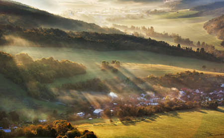 Aerial view of village in fog with golden sunbeams at sunrise in autumn. Beautiful rural landscape with road, buildings, foggy colorful trees. Slovakia Zdjęcie Seryjne