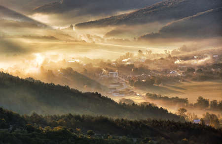Aerial view of village in fog with golden sunbeams at sunrise in autumn. Beautiful rural landscape with road, buildings, foggy colorful trees. Slovakia