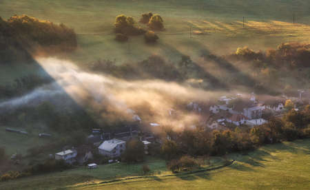 Countryside rural landscape with village over sunbeam in misty morning. Reklamní fotografie