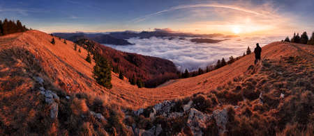 Panorama of the mountain landscape above clouds at sunset with sun Reklamní fotografie