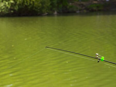 fishing rig: fishing pole with bells in the green calm river, bottom fishing line