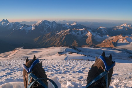 crampon: First person view to body and far landscape. Man legs in crampons take a rest on the top of mountain. Feet in trekking boots on the background of the Caucasus