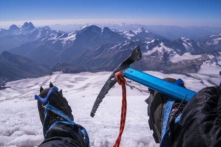 crampon: First person view to body and far landscape. Man legs in crampons with an ice axe take a rest on the top of mountain. Feet in trekking boots on the background of the Caucasus