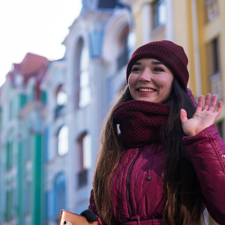 Pretty Smiling Brunette Girl Wearing Purple Winter Coat, Hat and Scarf, Walking by European Street at Winter Banque d'images