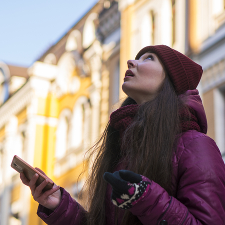 Pretty Brunette Girl Wearing Purple Winter Coat, Hat and Scarf, Walking by European Street at Winter, make Photos on Her Smartphone and Making Selfie