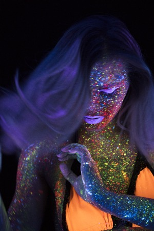 Portrait of Beautiful Fashion Woman in Neon UF Light. Model Girl with Fluorescent Creative Psychedelic MakeUp, Art Design of Female Disco Dancer Model in UV Stock Photo