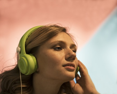 Portrait of Attractive Young Blonde Woman in Trench Trying Headphones Stock Photo