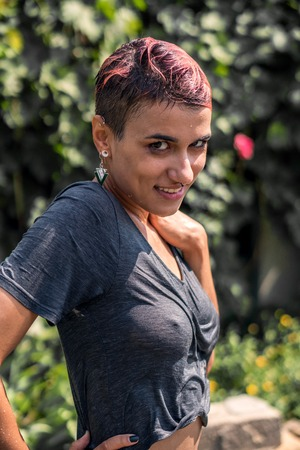 Young Pretty Pierced Girl in Wet shirt after Shower from the Hose in Garden. Summer Leisure and Wet t-Shirt. Standard-Bild