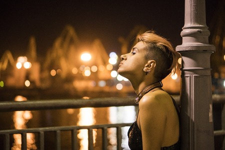 Girl sitting under the Night Lighter with Marine Port on background