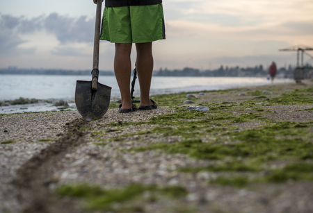 Path of a shovel behind a man searching for a precious metal using a metal detector on lonely beach at sunset time