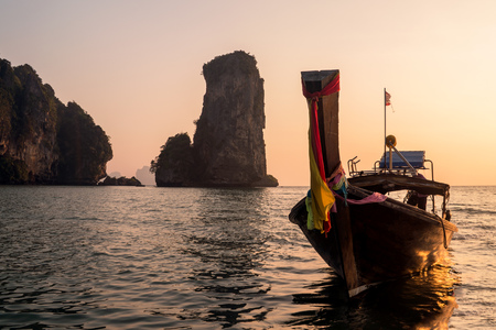 Beautiful sunset with silhouette of Traditional Longtail boat and High Rocks in the sea. Krabi, Thailand 版權商用圖片