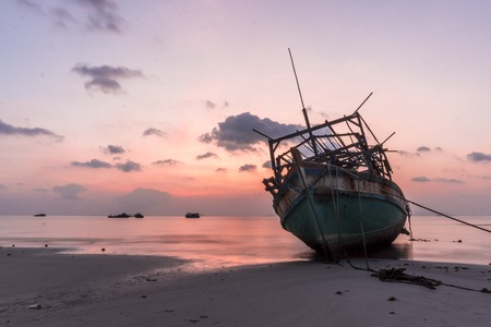 The old wooden ruined fishing boats set aground on the beach at Sunset time