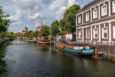 Traditional wooden sailing ships in water channel. Windmill behind a buildings. Old historic harbor of Schiedam, The Netherlands